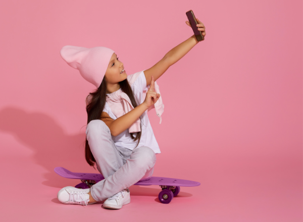 young girl taking a selfie: the effect social media filters have on childrens self esteem