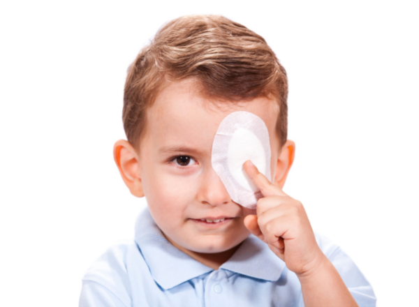 young boy wearing eye patch: Amblyopia causes and treatment of lazy eye in children