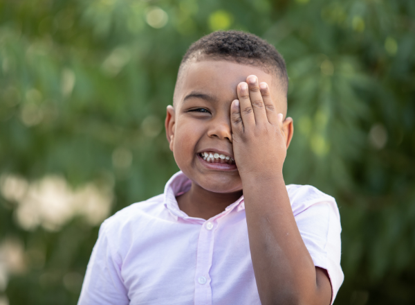boy covering one eye with his hand: Amblyopia causes and treatment of lazy eye in children