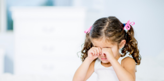 young girl rubbing her eyes: eye allergies in children